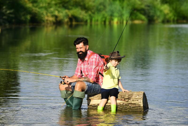 Generations ages: father and son. Family holiday and togetherness. Fishing in river. Old and Young. Father and son stock photography