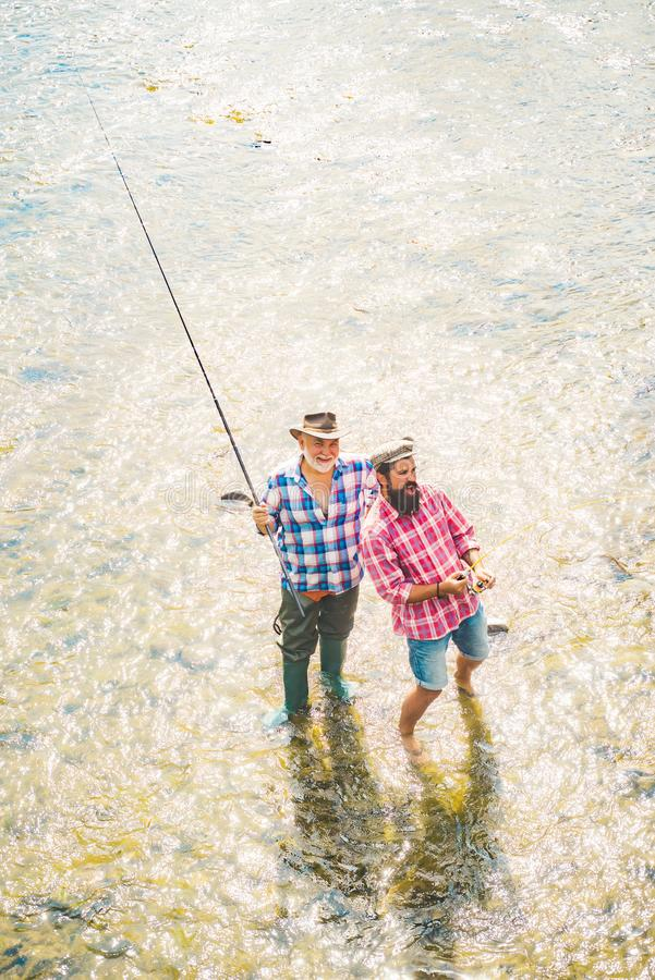 Generations ages: grandfather and father. Fishing in river. Young man and old mature man fly fishing. Father with son on royalty free stock photo