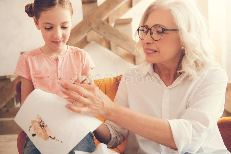 Nice smart woman teaching her granddaughter to embroider. Between generations. Nice pleasant smart women sitting together with her granddaughter and smiling stock image