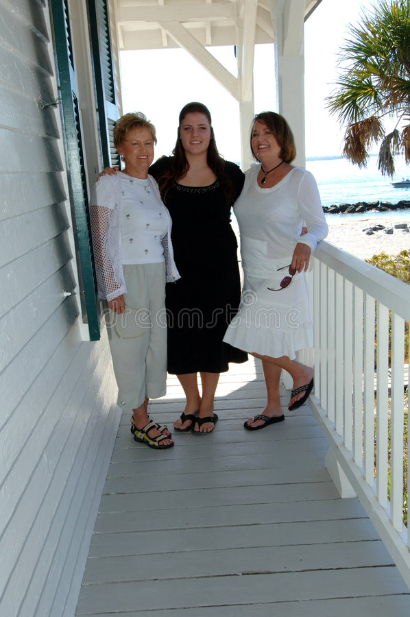 Generations of women on porch. Three women of different generations on the porch of a beach house stock images