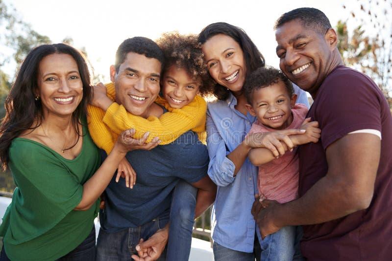 Generationsfamilie des Afroamerikaners drei, die zusammen im Garten, lächelnd zur Kamera spielt stockbild
