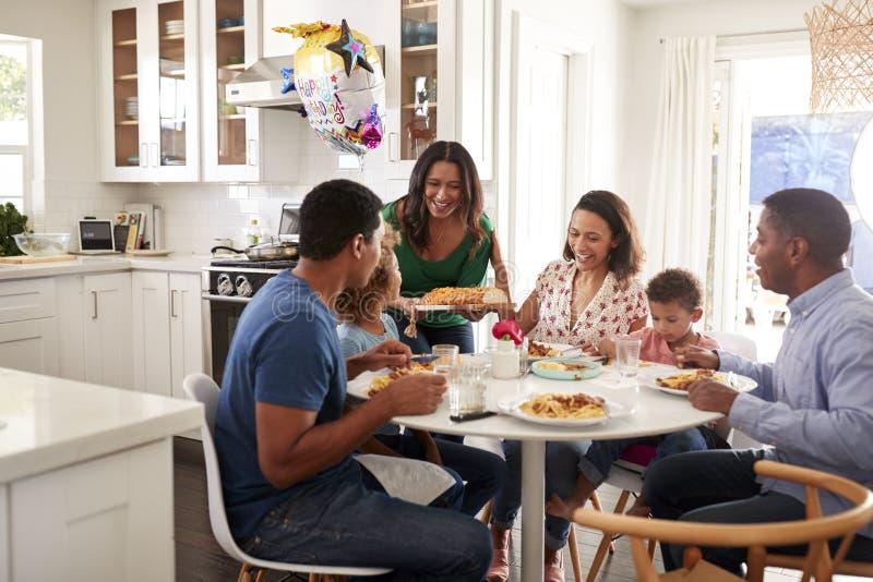 Generationsfamilie des Afroamerikaners drei, die zusammen am Küchentisch, mit dienender Nahrung der Großmutter sitzt lizenzfreies stockfoto