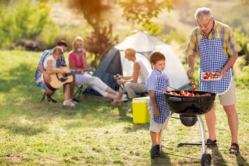 Generationsfamilie, die auf Grill kocht lizenzfreie stockfotografie