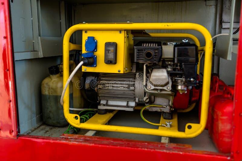 Generatore di corrente per benzina in una condizione d'abitazione gialla nel vano portaoggetti di un camion dei vigili del fuoco fotografia stock libera da diritti