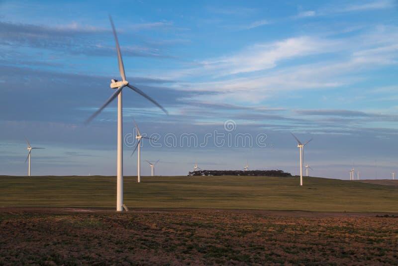 Generatori eolici che girano nella terra aperta dell'azienda agricola fotografie stock libere da diritti
