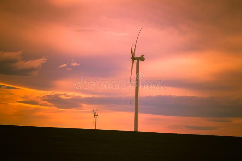 Generatori eolici contro un bello cielo di tramonto fotografia stock
