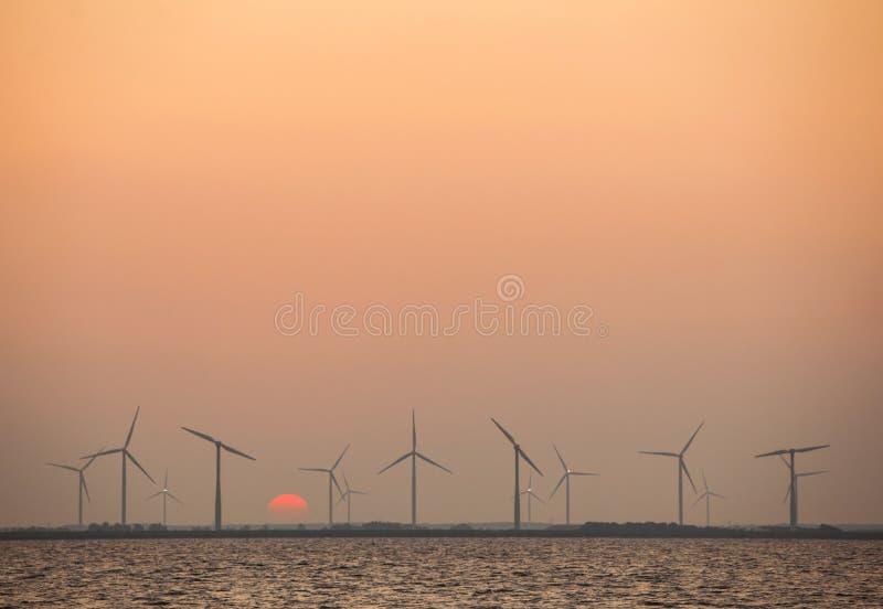 Generatori eolici e sol levante in cielo variopinto fotografie stock