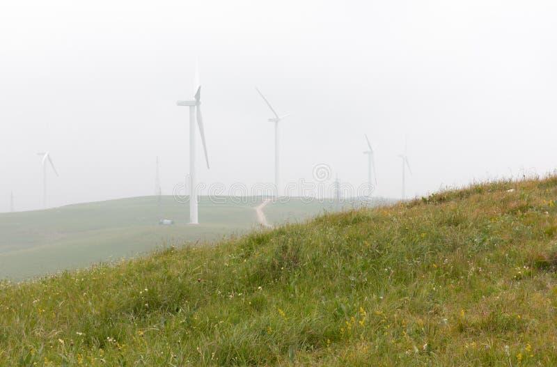 Generatori eolici a Huapo un giorno nebbioso di estate, contea di Qinyuan fotografia stock libera da diritti
