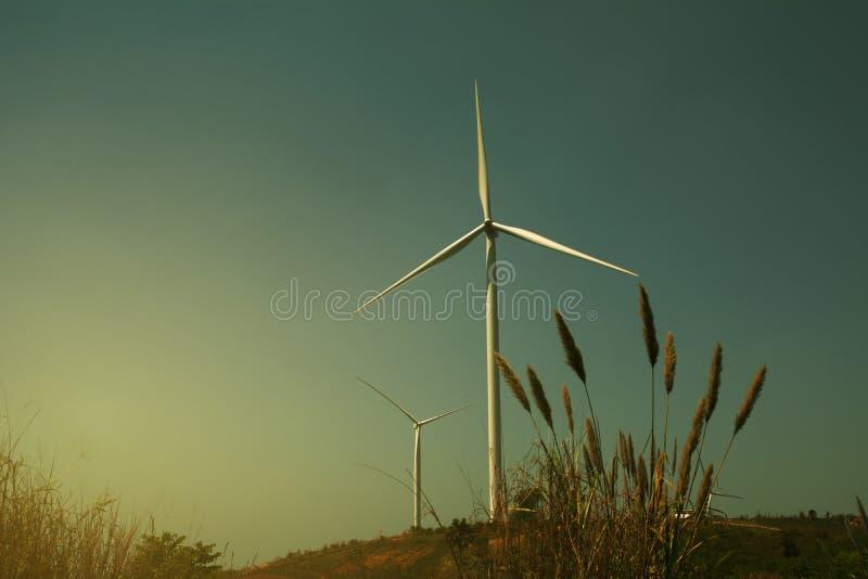 Generatori eolici sotto il cielo per il concetto di tecnologia Turbine di vento nel campo verde fotografia stock libera da diritti
