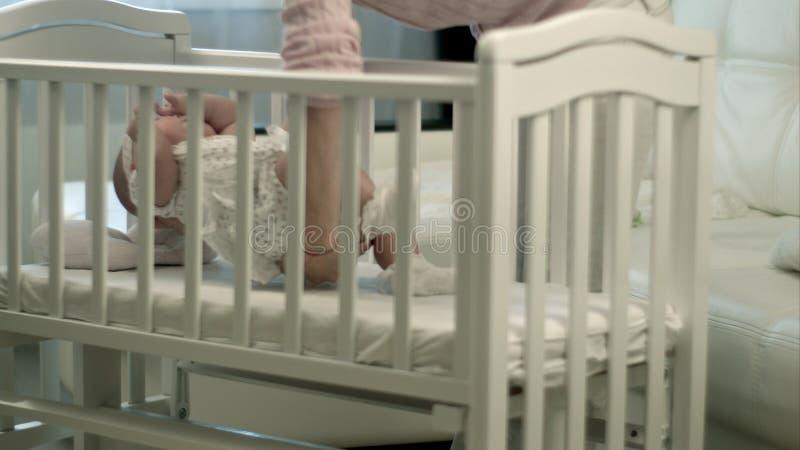 Generi accarezzare la sua neonata sveglia che dorme in una culla immagini stock