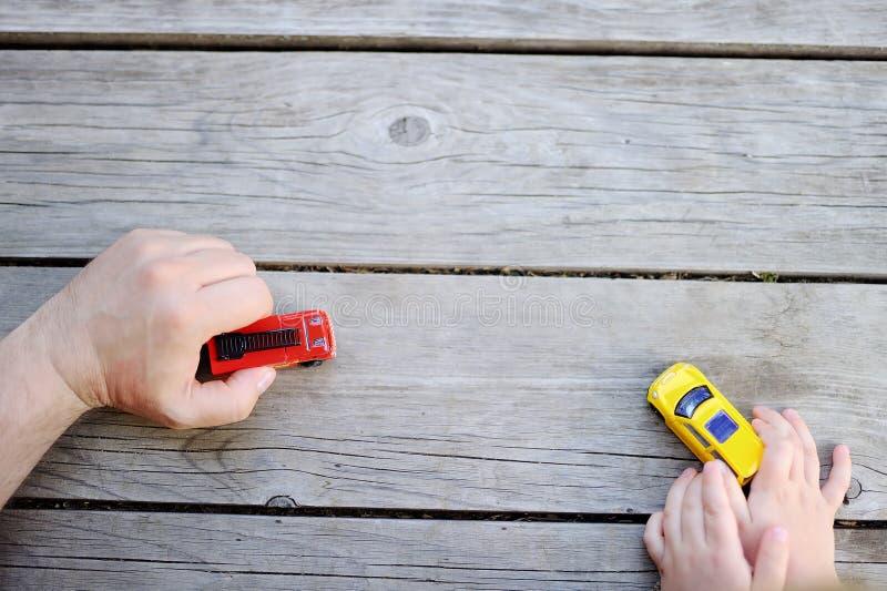 Generi con il suo piccolo figlio che gioca con le automobili del giocattolo immagini stock libere da diritti