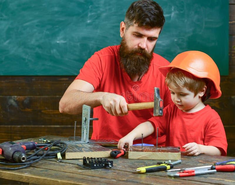 Generi con la barba che insegna al piccolo figlio ad utilizzare gli strumenti, martellanti, lavagna su fondo Concetto di paternit fotografia stock