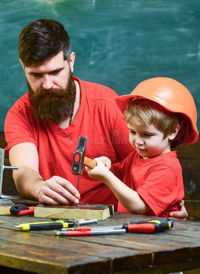 Generi con la barba che insegna al piccolo figlio ad utilizzare gli strumenti, martellanti, lavagna su fondo Ragazzo, bambino occ fotografia stock