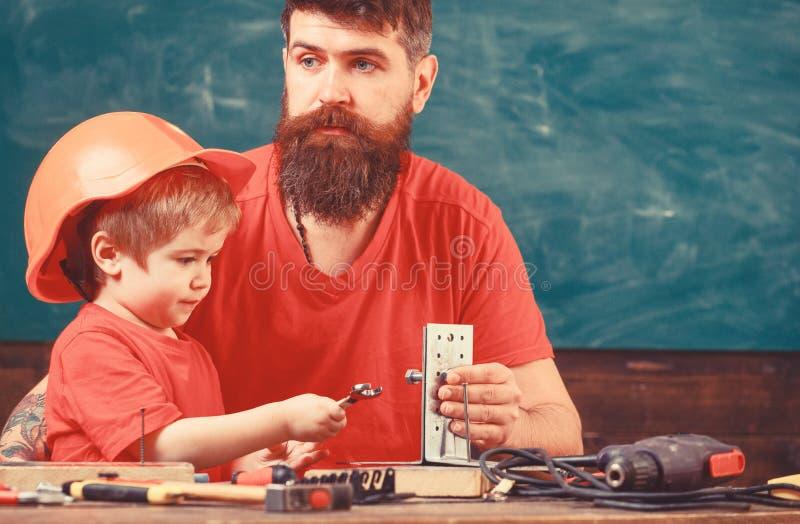 Generi con la barba che insegna al piccolo figlio a utilizzare gli strumenti in aula, lavagna su fondo Concetto del lavoro degli  fotografie stock