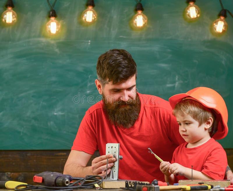 Generi con la barba che insegna al piccolo figlio a utilizzare gli strumenti in aula, lavagna su fondo Genera il concetto di aiut fotografie stock