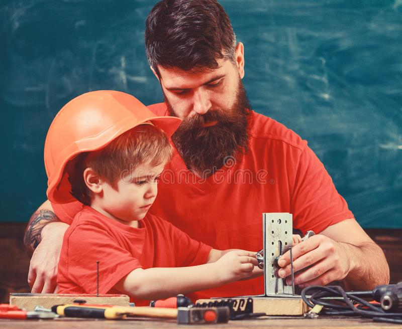 Generi con la barba ed il piccolo figlio nell'insegnamento dell'aula per utilizzare gli strumenti, lavagna su fondo Concetto del  fotografia stock