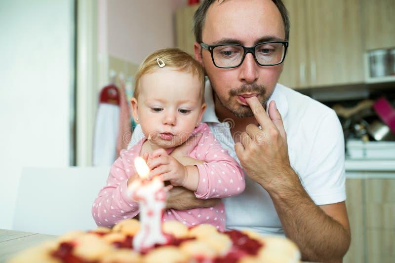 Generi con sua figlia sveglia che mangia la sua torta di compleanno fotografie stock