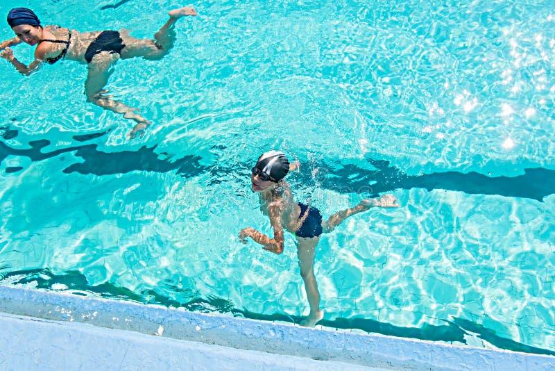 Generi dare al figlio una lezione di nuoto in stagno durante fotografia stock libera da diritti