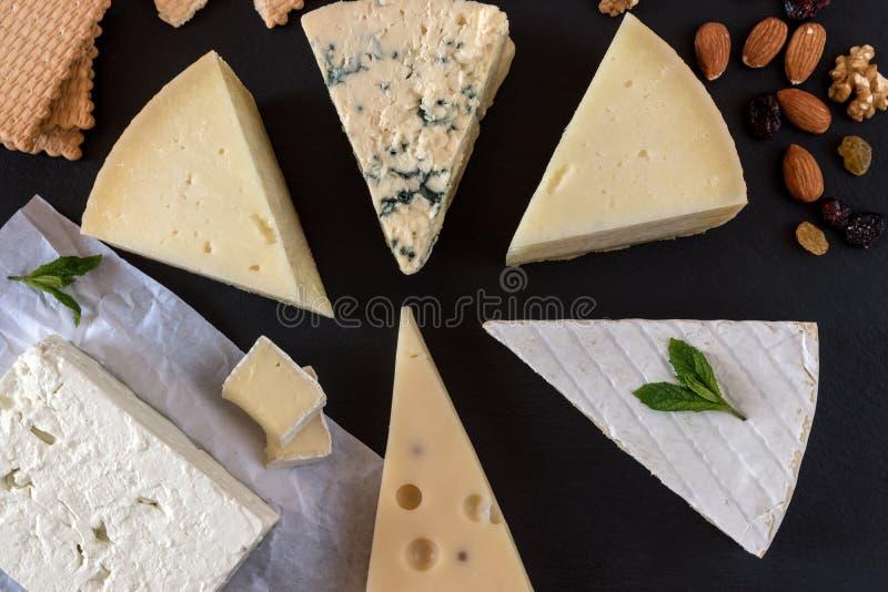 Generi differenti di formaggi sul bordo di pietra nero con i dadi fotografia stock
