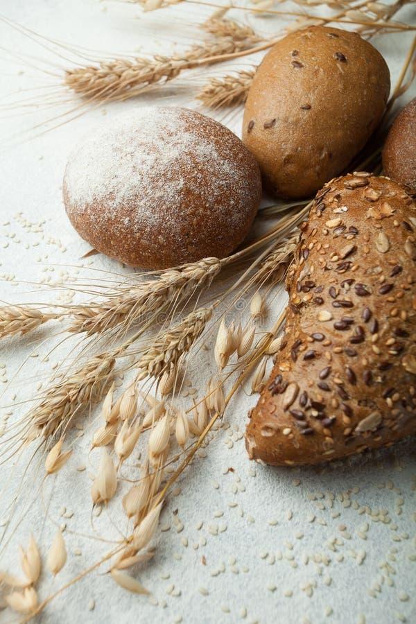 Generi differenti di pane di segale scuro su fondo bianco Pane intero con i semi fotografia stock libera da diritti