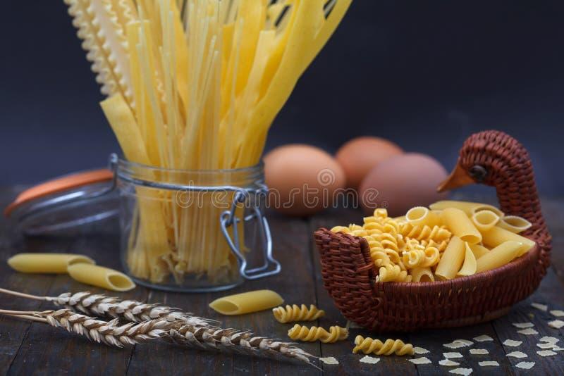 Generi differenti di tagliatelle, di spaghetti e di altra pasta con le uova immagine stock