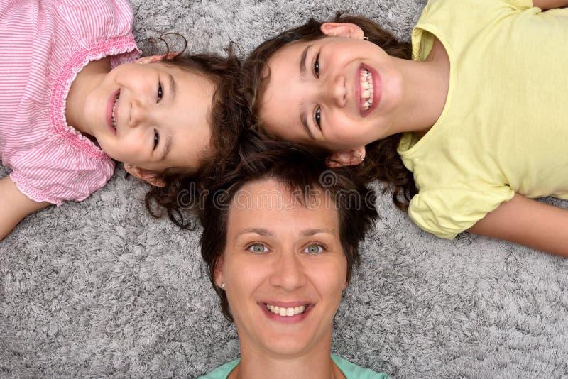 Generi e due figlie che si trovano sul tappeto immagine stock libera da diritti