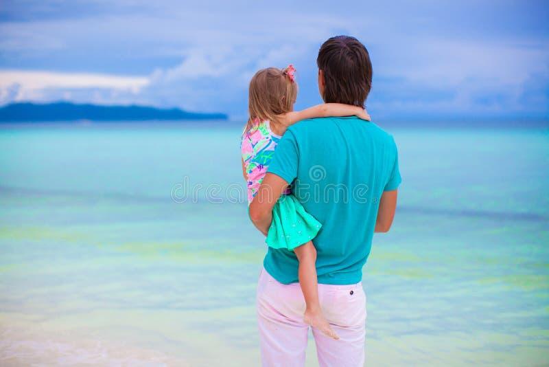 Generi e la sua piccola figlia che considera il mare fotografie stock