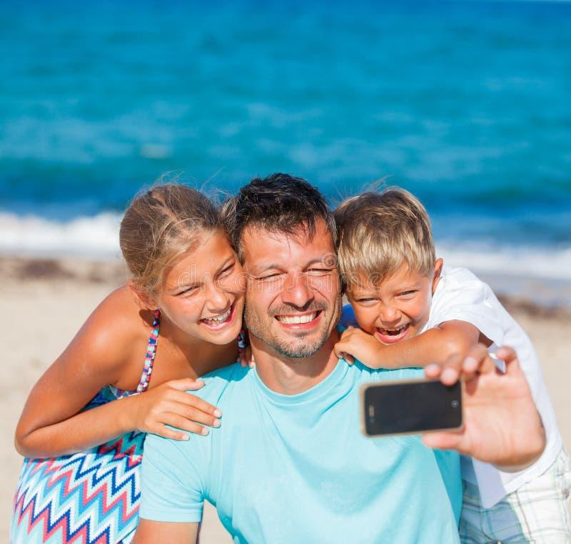 Generi ed i suoi bambini alla spiaggia che prende il selfie immagini stock