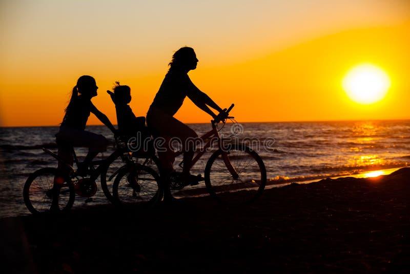 Generi ed i suoi bambini sulle siluette della bicicletta fotografia stock libera da diritti