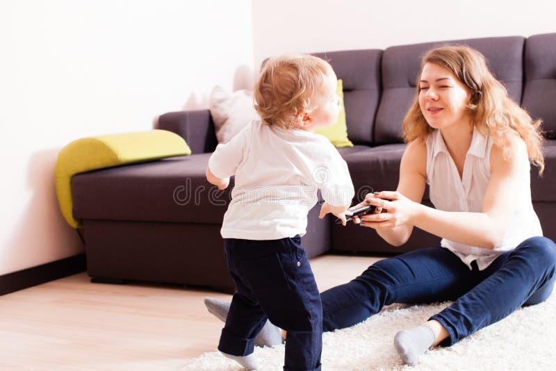 Generi ed il suo neonato che gioca sul pavimento immagini stock