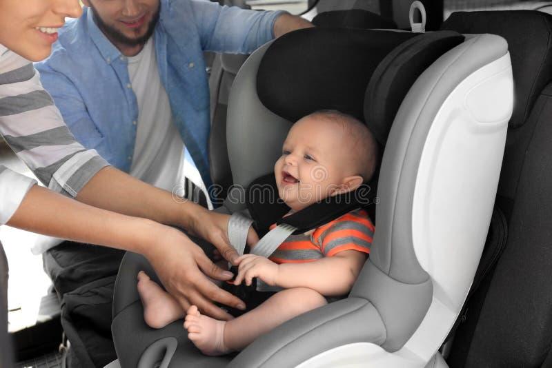 Generi il bambino della legatura al sedile della sicurezza del bambino dentro immagine stock libera da diritti