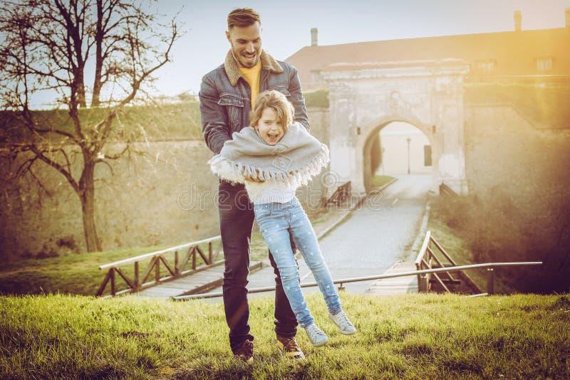 Generi il gioco con sua figlia nel parco Il padre gira il suo fotografia stock libera da diritti
