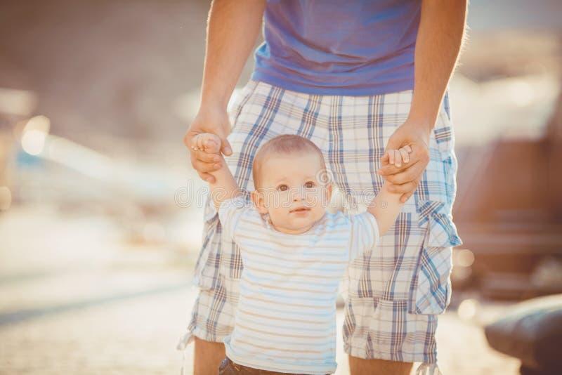 Generi il gioco con suo figlio sul pilastro vicino all'yacht club di estate. All'aperto fotografia stock