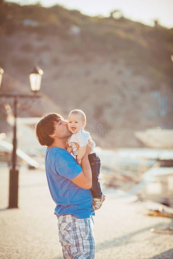 Generi il gioco con suo figlio sul pilastro vicino all'yacht club di estate. All'aperto immagine stock