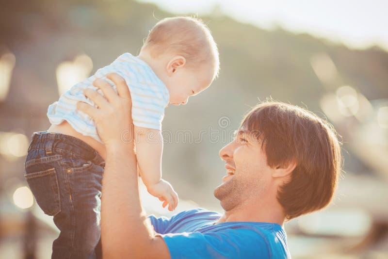 Generi il gioco con suo figlio sul pilastro vicino all'yacht club di estate. All'aperto fotografie stock libere da diritti
