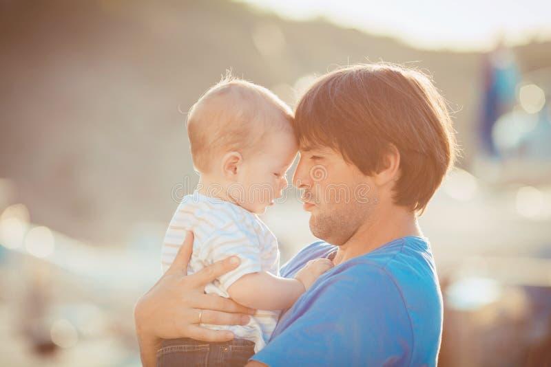 Generi il gioco con suo figlio sul pilastro vicino all'yacht club di estate. All'aperto immagini stock libere da diritti