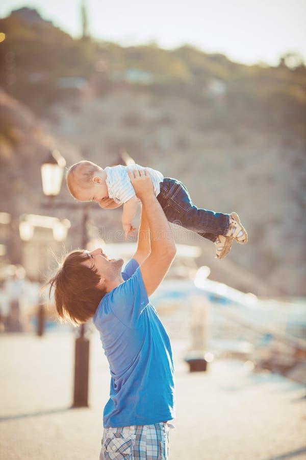 Generi il gioco con suo figlio sul pilastro vicino all'yacht club di estate. All'aperto fotografie stock