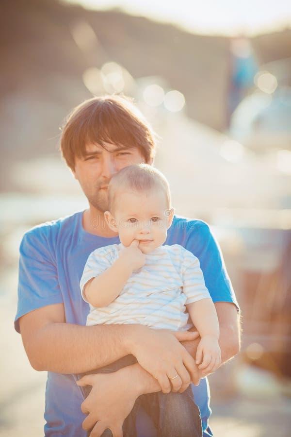 Generi il gioco con suo figlio sul pilastro vicino all'yacht club di estate. All'aperto fotografia stock libera da diritti