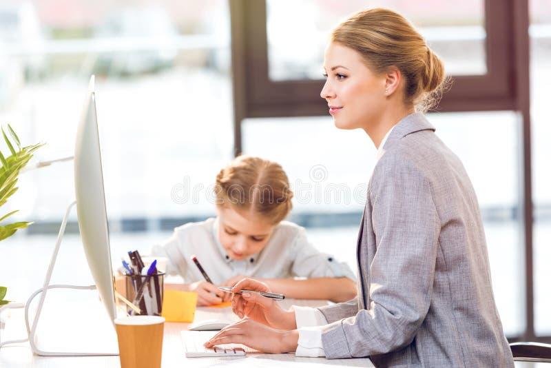 Generi il lavoro con il computer mentre sua figlia che assorbe l'ufficio di affari immagini stock libere da diritti