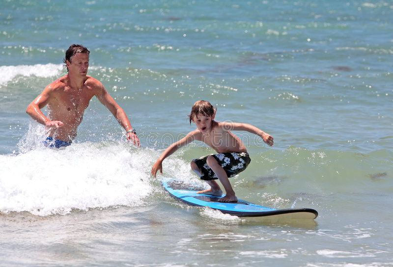 Generi insegnando al suo giovane figlio a come praticare il surfing fotografia stock