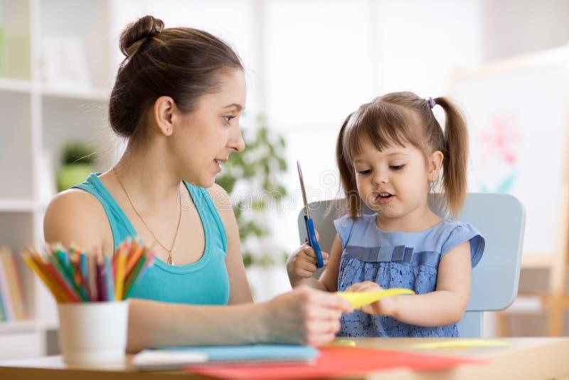 Generi l'aiuto del suo bambino tagliare la carta colorata fotografie stock