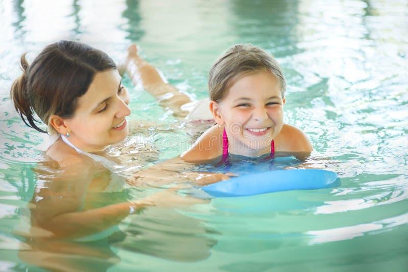 Generi l'apprendimento nuotare la sua piccola figlia in uno swimmin dell'interno immagine stock