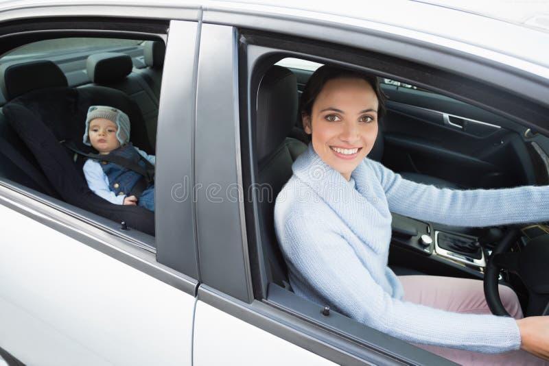 Generi l'azionamento con il suo bambino nella sede di automobile immagini stock libere da diritti