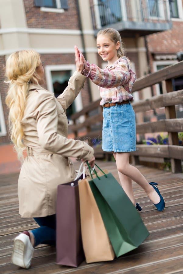 Generi la condizione su un ginocchio con i sacchetti della spesa e livello cinque dare alla sua piccola figlia fotografia stock