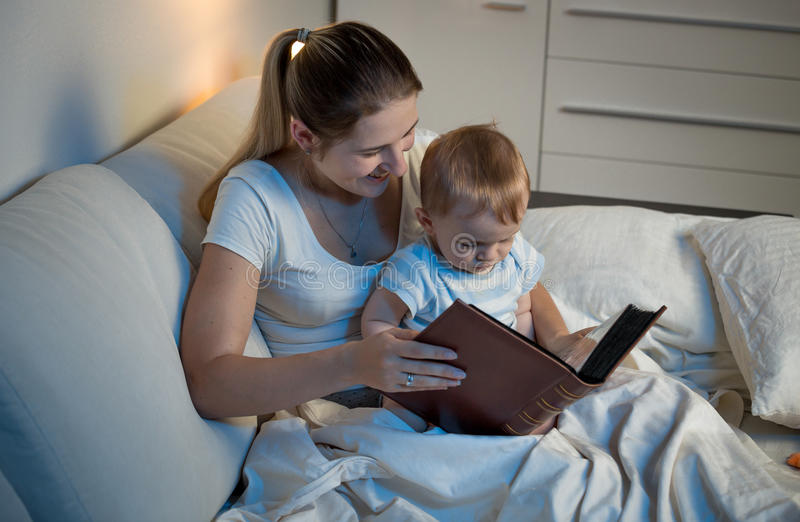Generi la narrazione al suo neonato adorabile al letto prima di andare immagine stock libera da diritti