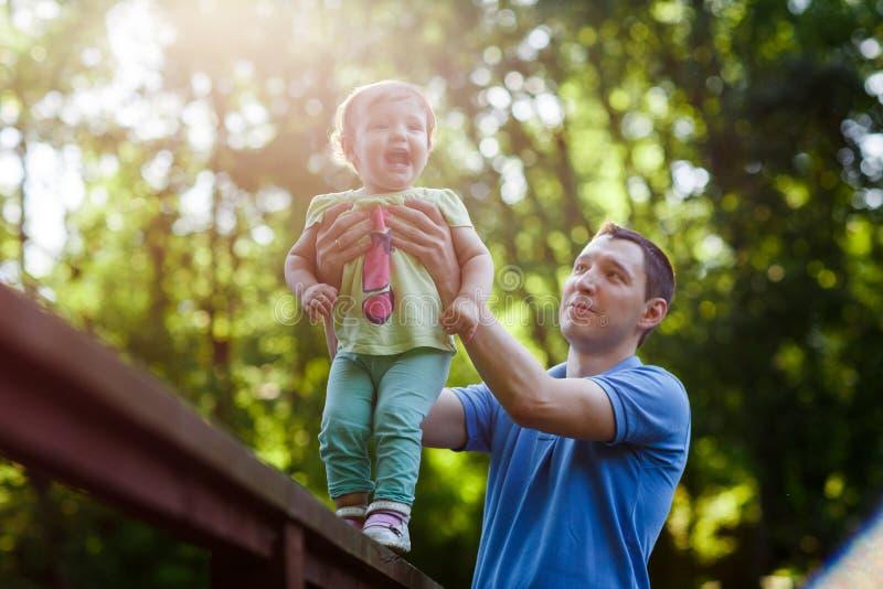 Generi la piccola figlia di sostegni che sta sul ponte in parco fotografie stock libere da diritti