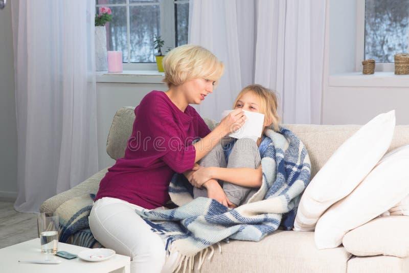 Generi la presa della cura del suo bambino malato, pulente il suo fronte con il fazzoletto immagine stock libera da diritti