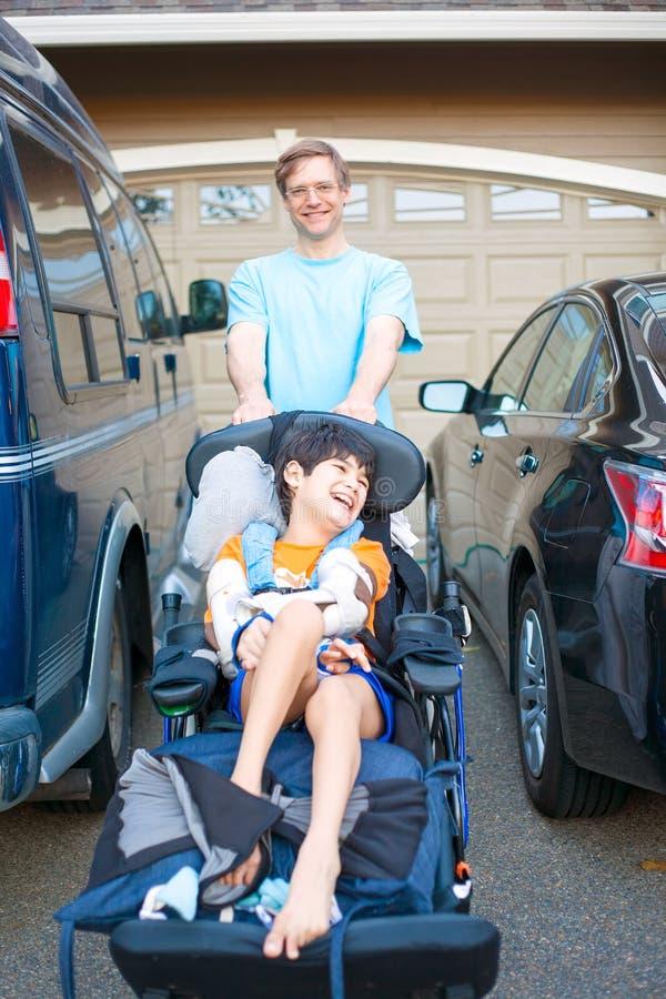 Generi la spinta del figlio disattivato in sedia a rotelle dopo le automobili in strada privata immagini stock libere da diritti