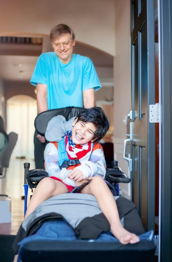 Generi la spinta del figlio disattivato in sedia a rotelle fuori l'entrata principale immagini stock libere da diritti