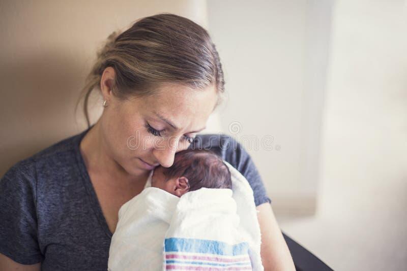 Generi la tenuta del suo bambino prematuro neonato nell'ospedale immagini stock libere da diritti